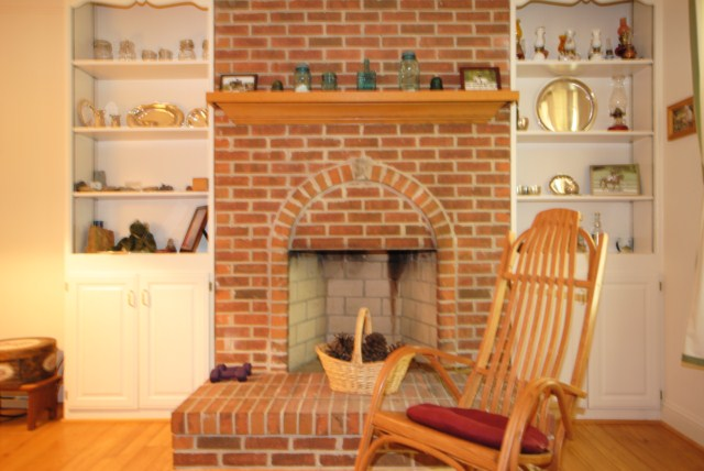 Wood burning fireplace flanked by builtin bookcases