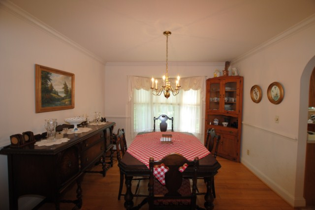 Dining room with chair rail, crown molding and bay window.